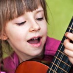 Mädchen mit Kindergitarre singt